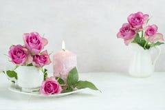 Todavía vida con las rosas y la vela Imagenes de archivo