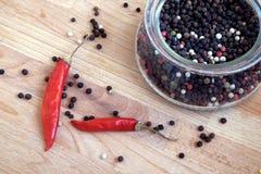 Todavía vida con las semillas de la paprika de la pimienta de chiles roja y de la pimienta negra dentro del tarro de cristal redo Imagen de archivo