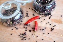 Todavía vida con las semillas de la paprika de la pimienta de chiles roja y de la pimienta negra dentro del tarro de cristal redo Imagen de archivo libre de regalías