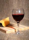 Todavía vida con las uvas de vino rojo y los chees en la tabla de madera Imagen de archivo