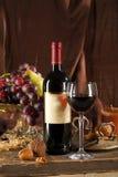Todavía vida con las uvas, las tuercas, una botella y un vidrio Fotografía de archivo libre de regalías