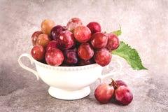 Todavía vida con las uvas rojas en la taza blanca del vintage en piedra sucia Foto de archivo libre de regalías