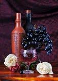 Todavía vida con las uvas y las botellas de un vino Imagen de archivo