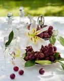 Todavía vida con las uvas y las orquídeas en el jardín Imágenes de archivo libres de regalías