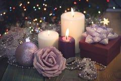 Todavía vida con las velas ardientes, las decoraciones de la Navidad y una caja de regalo Fotos de archivo libres de regalías