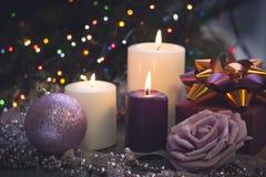 Todavía vida con las velas ardientes, las decoraciones de la Navidad y una caja de regalo Imagen de archivo