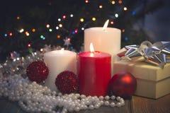 Todavía vida con las velas ardientes, las decoraciones de la Navidad y una caja de regalo Foto de archivo libre de regalías