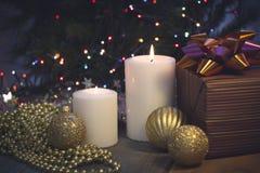 Todavía vida con las velas ardientes, las decoraciones de la Navidad y una caja de regalo Fotografía de archivo libre de regalías