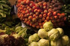 Todavía vida con las verduras en el mercado del pueblo: una diapositiva de la col verde, una cesta de zanahorias anaranjadas bril Fotografía de archivo libre de regalías