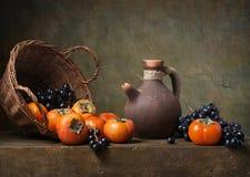 Todavía vida con los caquis y las uvas Imagen de archivo libre de regalías