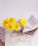 Todavía vida con los chrysathemums y los libros amarillos foto de archivo