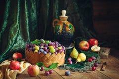 Todavía vida con los ciruelos en una cesta y las frutas en estilo rústico Imagen de archivo libre de regalías