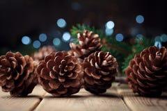 Todavía vida con los conos del pino y rama de árbol de abeto en la tabla de madera rústica Papá Noel en un trineo Fotografía de archivo libre de regalías