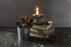 Todavía vida con los conos, los libros y las velas Fotografía de archivo libre de regalías