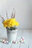 Todavía vida con los crisantemos amarillos y los huevos del este en un fondo blanco Fotos de archivo