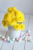 Todavía vida con los crisantemos amarillos y los huevos del este en un fondo blanco Imagenes de archivo