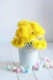 Todavía vida con los crisantemos amarillos y los huevos del este en un fondo blanco Imagen de archivo