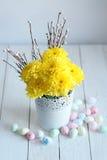 Todavía vida con los crisantemos amarillos y los huevos del este en un fondo blanco Foto de archivo