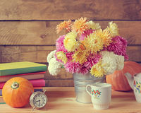 Todavía vida con los crisantemos, las calabazas, las mercancías, los libros y un ala Foto de archivo