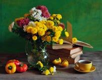 Todavía vida con los crisantemos y los libros foto de archivo