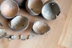 Todavía vida con los fragmentos de cáscara quebrados del coco en la tabla de madera marrón Foto de archivo