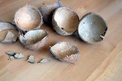 Todavía vida con los fragmentos de cáscara quebrados del coco en la tabla de madera marrón Imagen de archivo