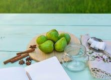 Todavía vida con los higos, proceso de cocinar del atasco Los higos verdes frescos en el fondo de madera, rodeado por las especia Fotografía de archivo libre de regalías