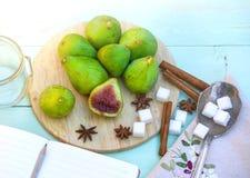 Todavía vida con los higos, proceso de cocinar del atasco Los higos verdes frescos en el fondo de madera, rodeado por las especia Fotos de archivo