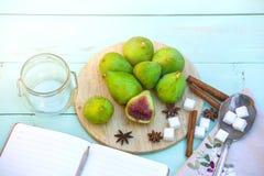 Todavía vida con los higos, proceso de cocinar del atasco Los higos verdes frescos en el fondo de madera, rodeado por las especia Imagen de archivo libre de regalías