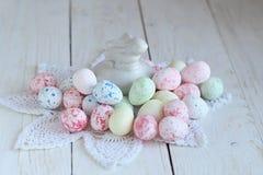 Todavía vida con los huevos de Pascua coloridos en una textura de madera blanca Fotografía de archivo