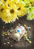 Todavía vida con los huevos de Pascua en cesta y el ramo de flores Foto de archivo libre de regalías