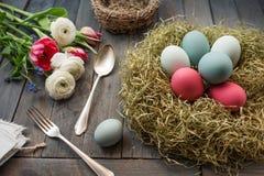 Todavía vida con los huevos de Pascua en una jerarquía y flores Fotografía de archivo