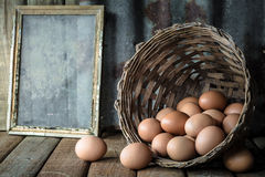 todavía vida con los huevos en la cesta de bambú en la tabla de madera Fotos de archivo libres de regalías