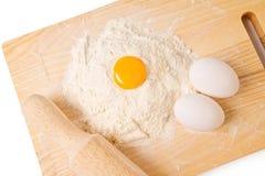 Todavía vida con los huevos, la harina y la tarjeta de madera Foto de archivo