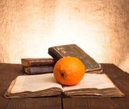 Todavía vida con los libros anaranjados y viejos en la tabla de madera vieja Fotos de archivo libres de regalías