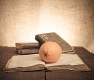 Todavía vida con los libros anaranjados y viejos en la tabla de madera vieja entonado Fotografía de archivo