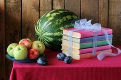 Todavía vida con los libros, los ciruelos, una sandía y las manzanas Fotos de archivo libres de regalías