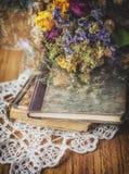 Todavía vida con los libros viejos, el ramo seco y el cordón en la madera Fotos de archivo