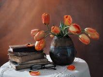 Todavía vida con los libros viejos y los tulipanes en un florero oscuro Fotos de archivo
