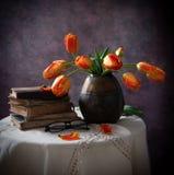 Todavía vida con los libros viejos y los tulipanes en un florero oscuro Imagen de archivo libre de regalías