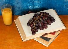 Todavía vida con los libros y un manojo de uvas Fotografía de archivo libre de regalías