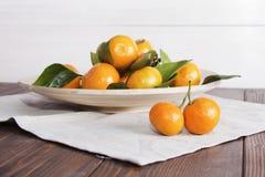 Todavía vida con los mandarines de las mandarinas en la placa Foto de archivo libre de regalías