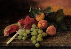 Todavía vida con los melocotones, las uvas y la sandía madura Imagen de archivo libre de regalías