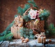 Todavía vida con los presentes en estilo del vintage Cajas adornadas, cesta, árbol de abeto, juguetes, nueces, almendras Imagen de archivo