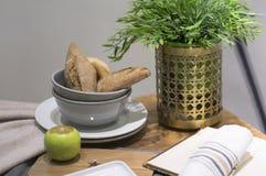 Todavía vida con los rollos de pan, Apple, una flor en la tabla Imagen de archivo libre de regalías