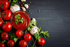 Todavía vida con los tomates, el ajo, el perejil, la salsa de tomate y la pimienta en los tableros de madera negros Imagen de archivo
