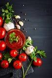Todavía vida con los tomates, el ajo, el perejil, la salsa de tomate y la pimienta en los tableros de madera negros Foto de archivo