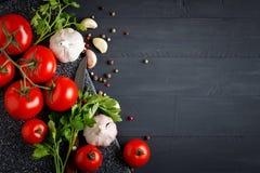 Todavía vida con los tomates, el ajo, el perejil y la pimienta en los tableros de madera negros Imágenes de archivo libres de regalías