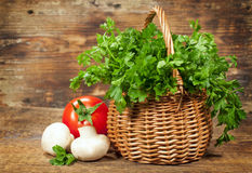 Todavía vida con los tomates, las setas y una cesta con perejil Imagenes de archivo