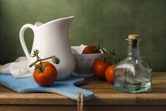 Todavía vida con los tomates y el jarro blanco Foto de archivo